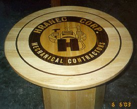 round Maple contractors table with a inlaid Corp. logo